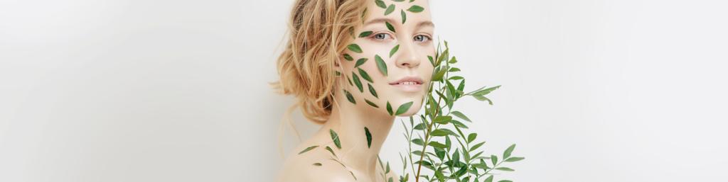 Blonde Frau deren Gesicht mit Olivenblättern bedeckt ist
