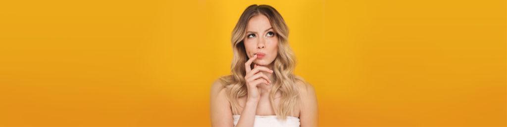 Blonde Frau überlegt vor gelbem Hintergrund