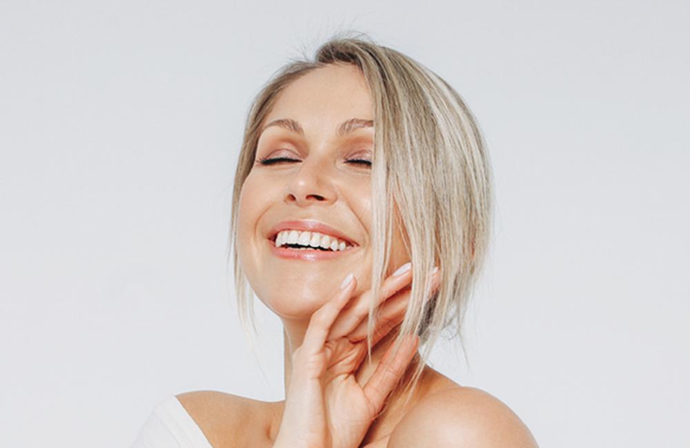 Blonde lachende Frau berührt mit der Hand ihr Gesicht
