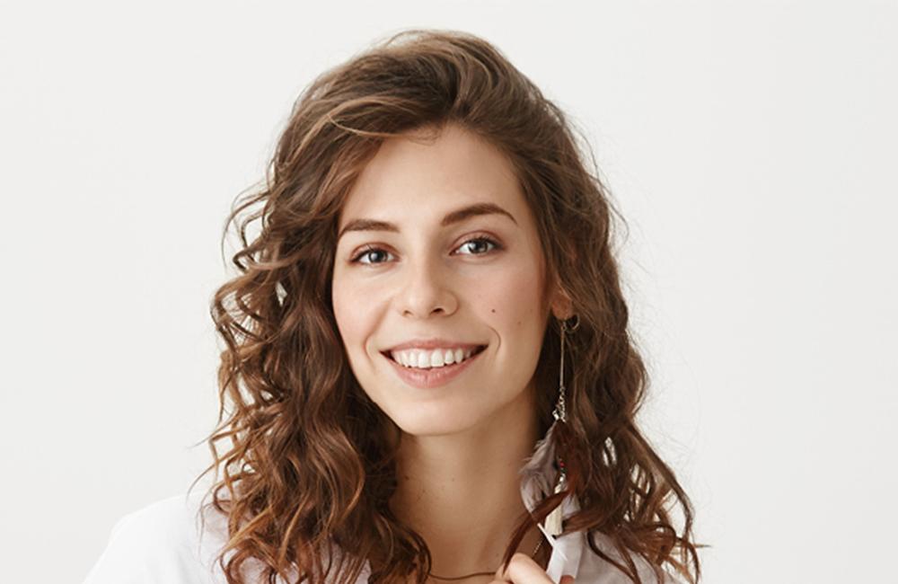 Frau mit brünetten Locken lächelt in die Kamera
