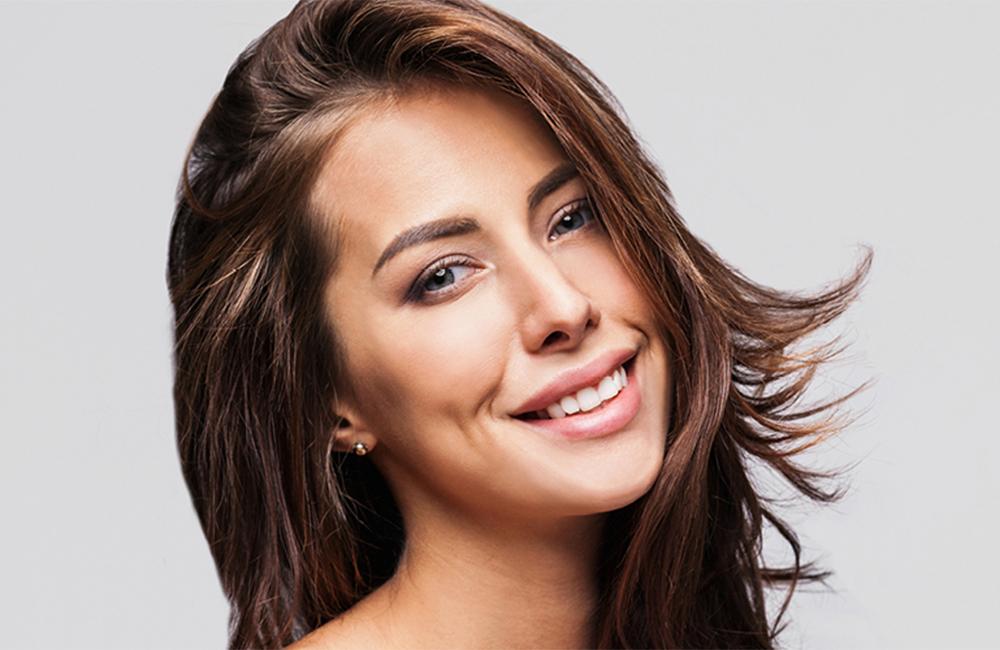 Brünette Frau mit schöner Haut lächelt in die Kamera