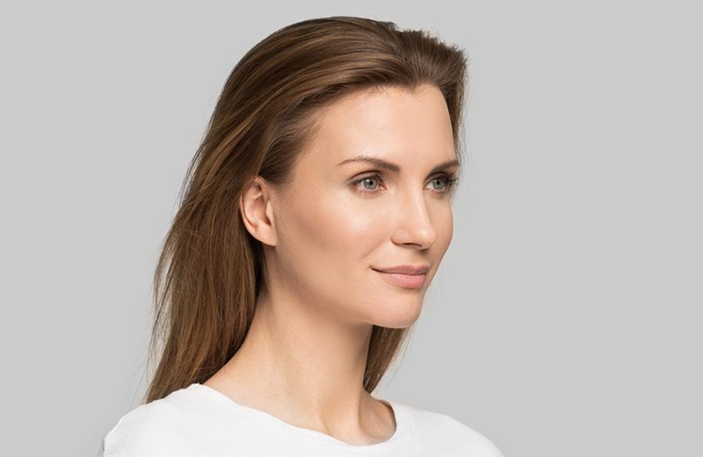 Brünette Frau mit schöner Haut trägt weißes Oberteil