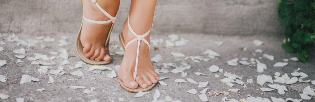 Schöne Füßen in weißen Sandalen