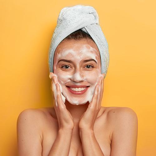 Junge Frau reinigt ihr Gesicht mit Reinigungsschaum