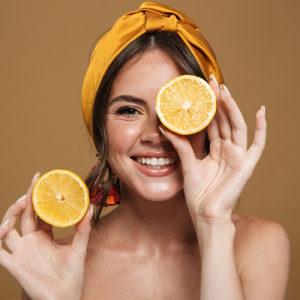 Lächelnde, brünette Frau hält Zitronenscheiben in der Hand
