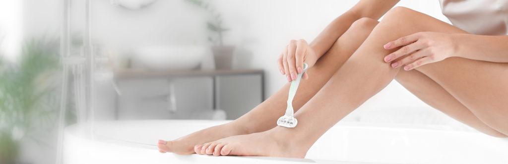 Frau rasiert sich auf dem Rand der Badewanne die Beine