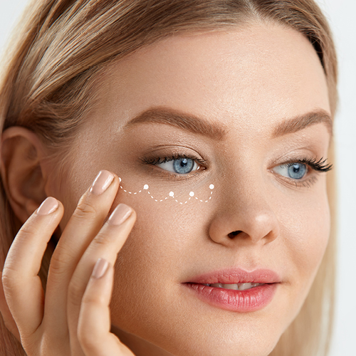 Frau trägt Augenpflege unter dem Auge