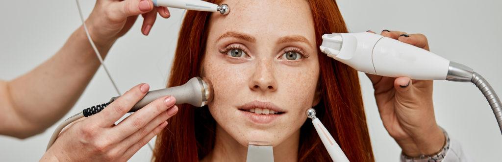 Hände halten Geräte für apparative Behandlungen in das Gesicht einerothaarigen Frau