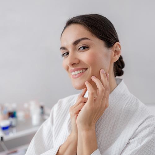 Frau im Bademantel lächelt und berührt ihre gepflegte Haut im Gesicht