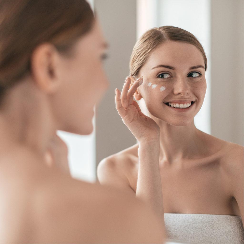 Frau verteilt Creme auf ihrem Gesicht