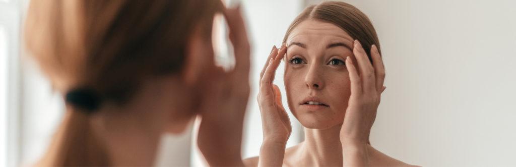 Frau betrachtet ihre Haut im Spiegel