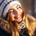 Lächelnde Frau bei Sonnenschein im verschneiten Wald