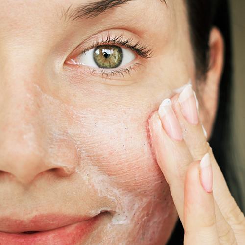 Frau verteilt Fruchtsäure-Creme auf ihrem Gesicht