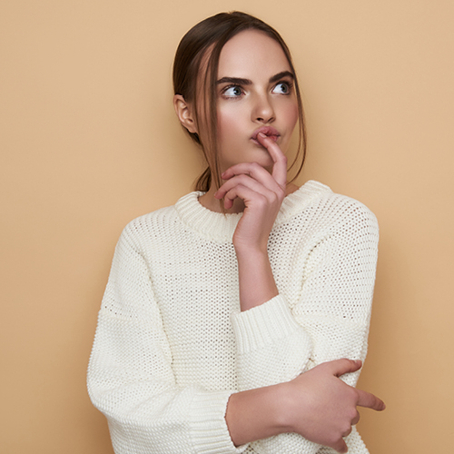 June Frau in weißem Pullover schaut nachdenklich zur Seite