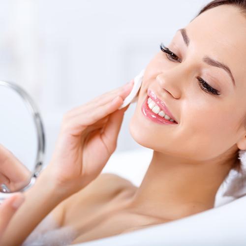 Brünette Frau schminkt sich in der Badewanne ab