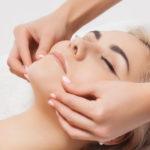 Kosmetikerin trägt Gesichtspeeling auf