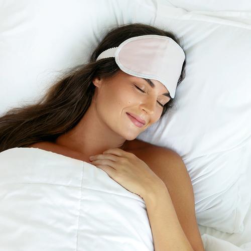 Schlafende Frau mit Schlafmaske im Bett