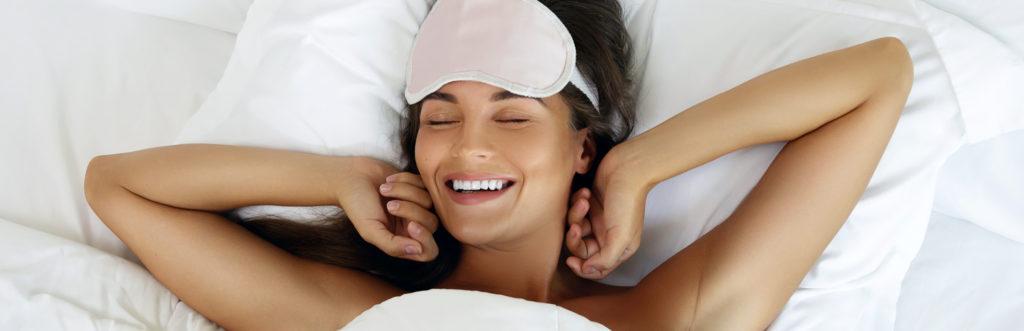 Lächelnde Frau mit Schlafmaske im Bett