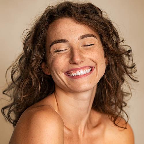 braunhaarige Frau lacht mit geschlossenen Augen