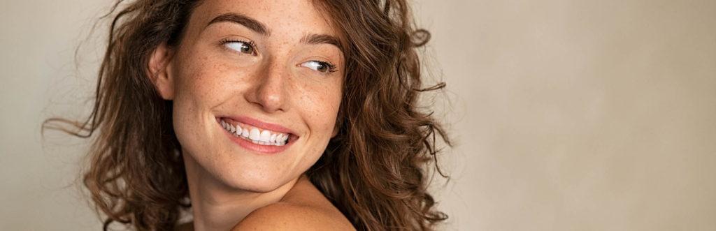 braunhaarige Frau schaut lächelnd zur Seite