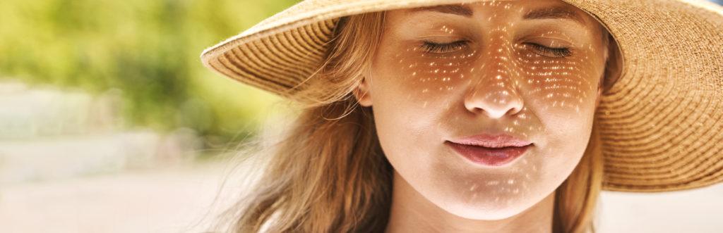 Frau mit Sonnenhut schließt die Augen