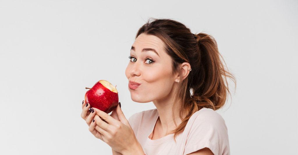 Frau beißt in einen roten Apfel