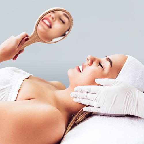 Frau bei der Kosmetikbehandlung schaut in einen Handspiegel