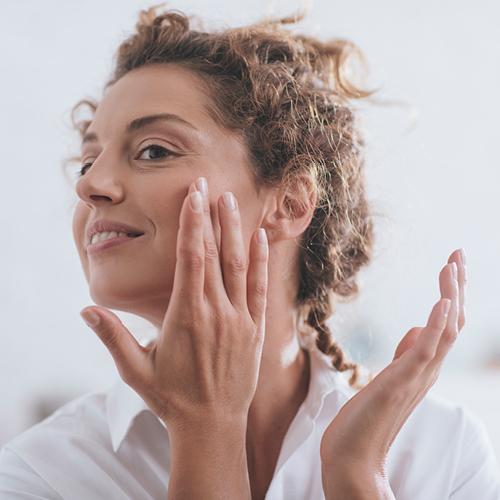 Frau cremt ihre Wange ein