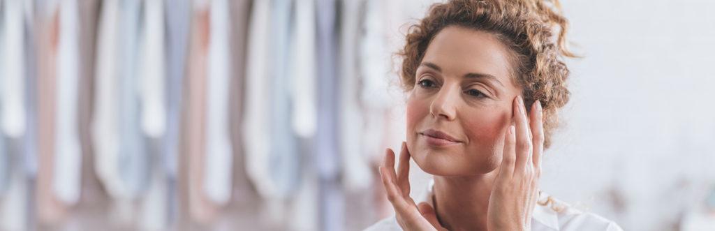 Frau berührt mit beiden Händen ihr Gesicht