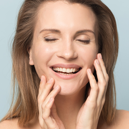 lachende Frau berührt ihr Gesicht