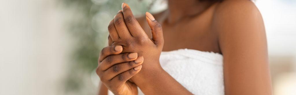 Frau in Handtuch berührt ihre Hände